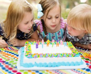 Children blowing candles on a cake out